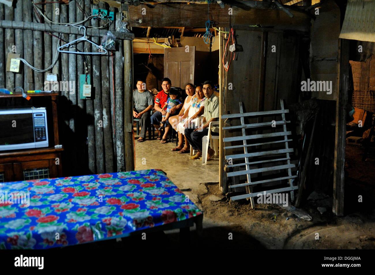 Famille d'un couple qui travaille dans l'industrie du tourisme, les gens assis dans une humble cabane en bois dans la nuit Photo Stock