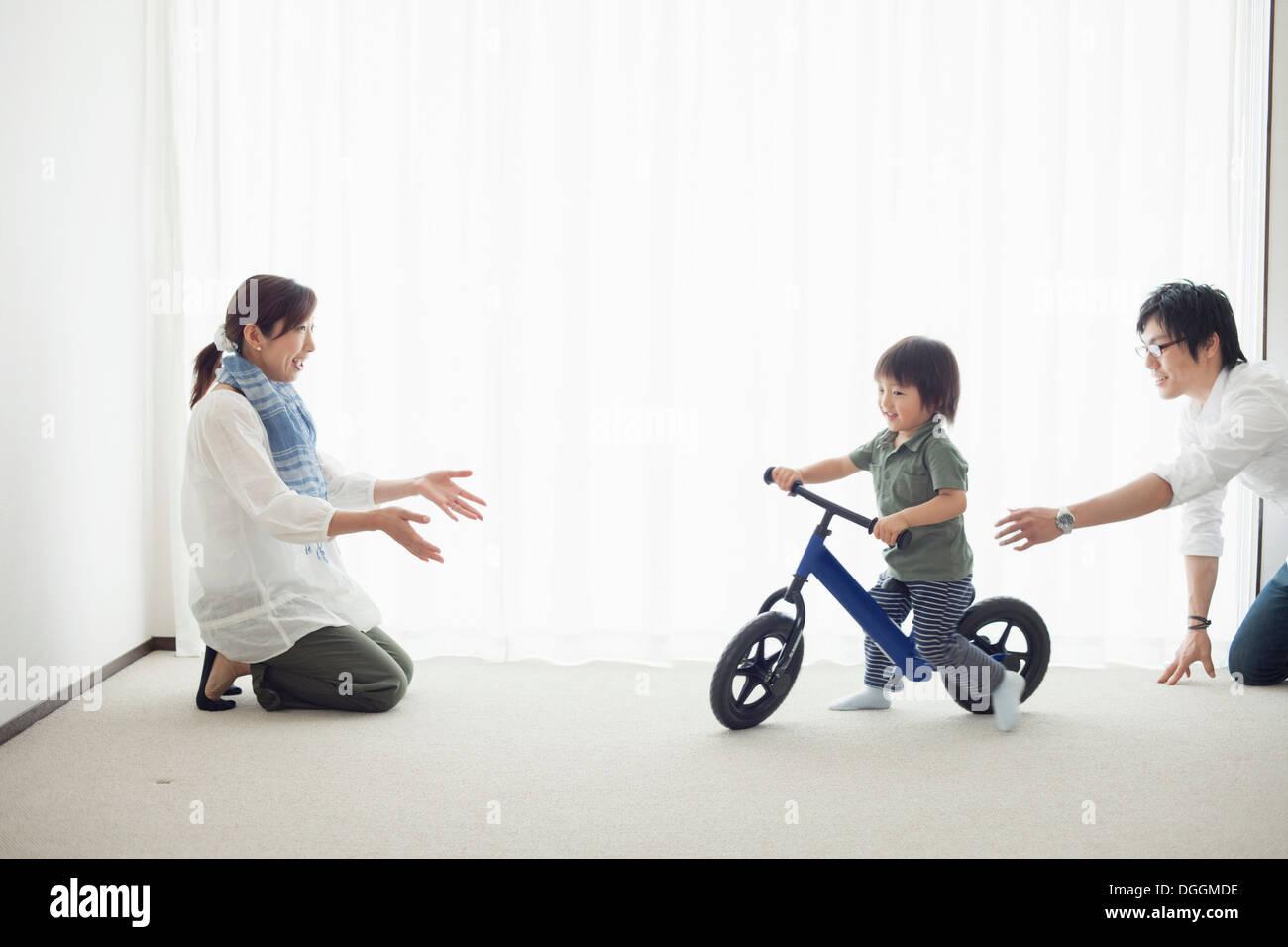 Les parents avec son fils à apprendre à faire du vélo location Banque D'Images