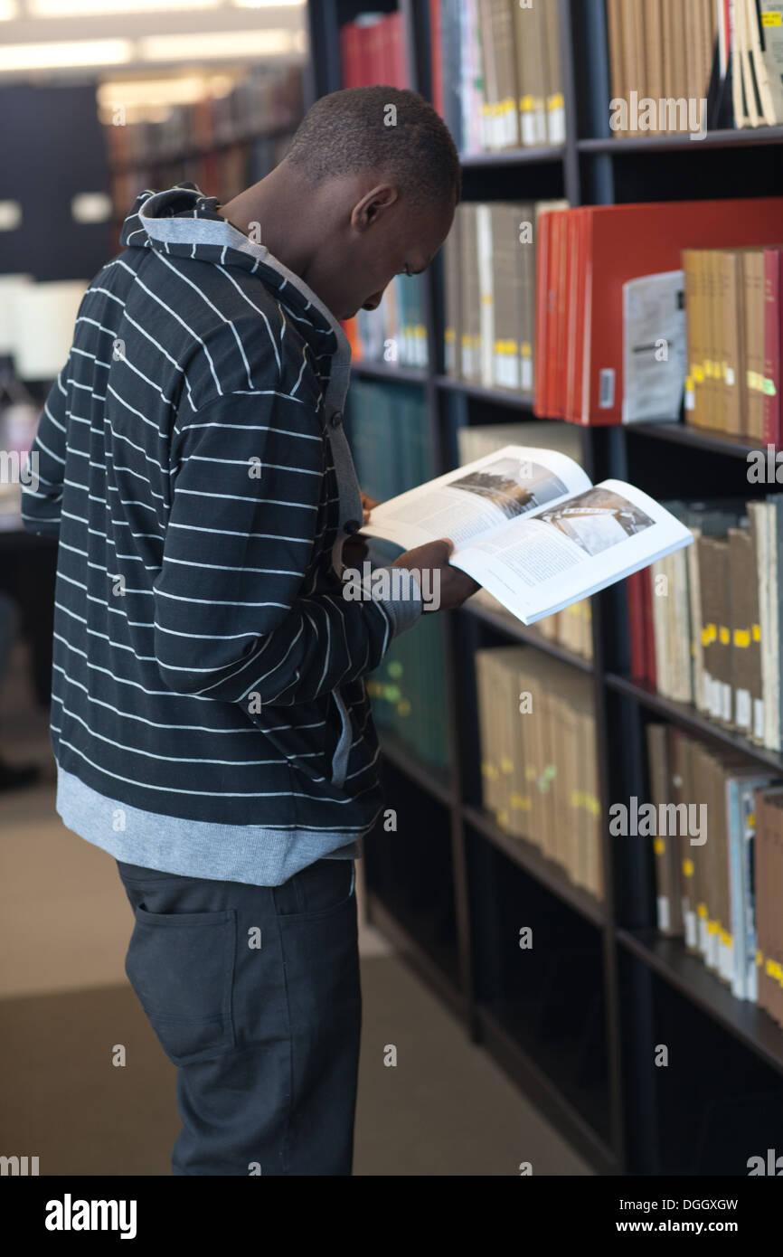 Jeune homme black college student recherche articles dans bibliothèque de l'école. Banque D'Images