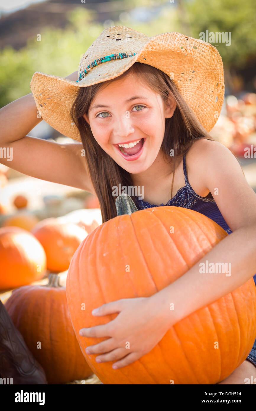 Preteen Girl Holding A large à la citrouille citrouille dans un cadre rustique. Photo Stock