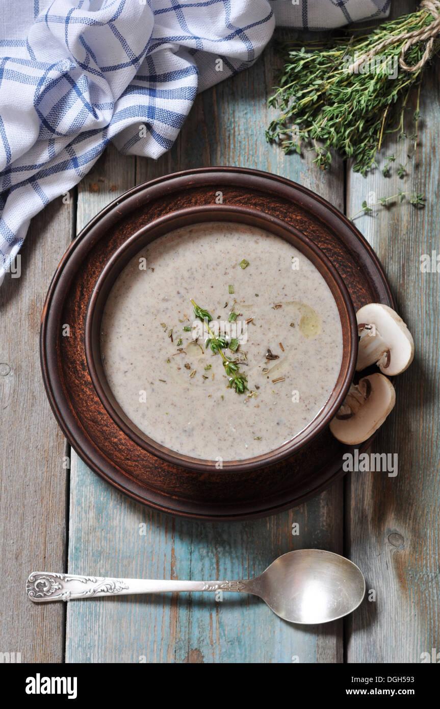 Crème de champignons soupe aux herbes dans brown bol sur fond de bois Photo Stock