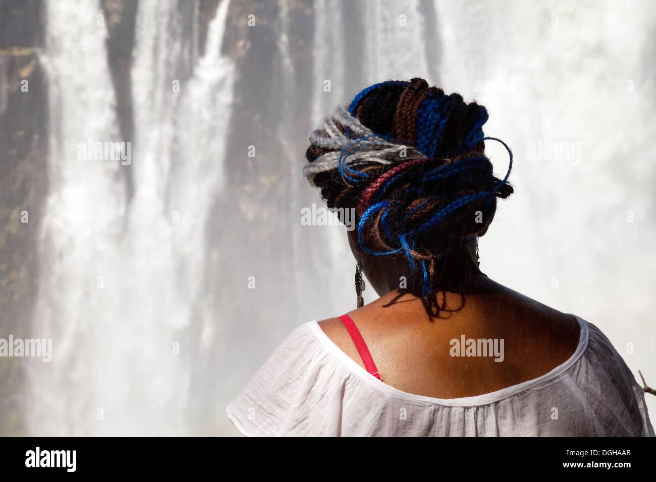 Le Zimbabwe, l'Afrique, une petite fille africaine locale regardant le Victoria Falls. Photo Stock