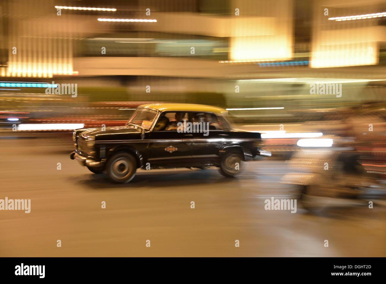 Taxi en mouvement sur une rue la nuit, Mumbai, Maharashtra, Inde Photo Stock