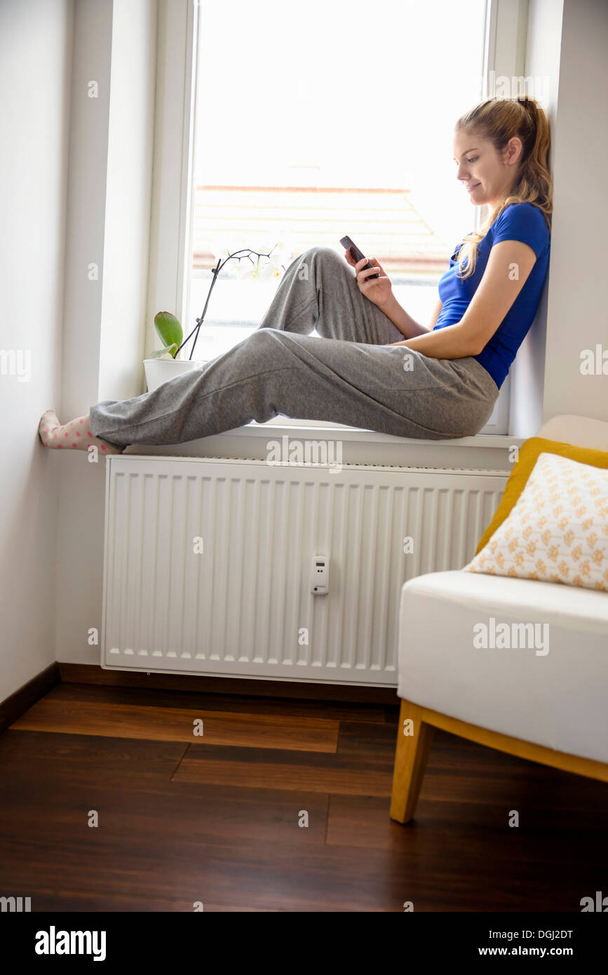 Young woman sitting on windowsill using cell phone Photo Stock
