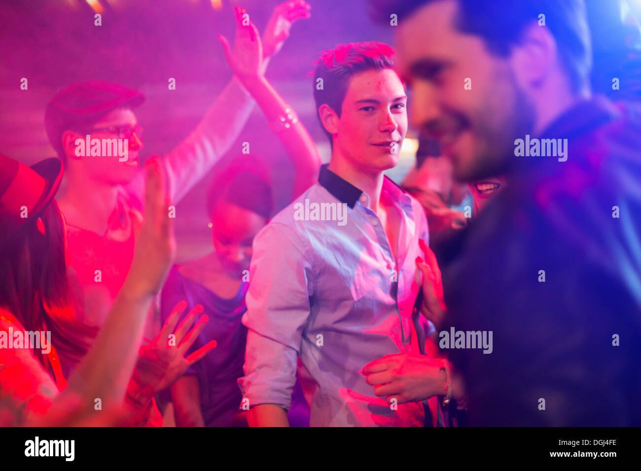 Teenage boy entouré par groupe de personnes dancing at party Photo Stock