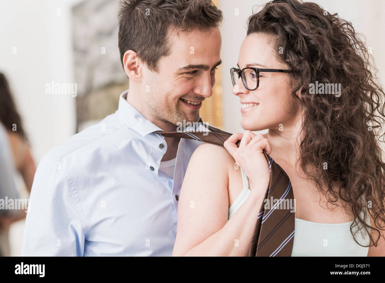 Mid adult woman pulling man's tie Photo Stock