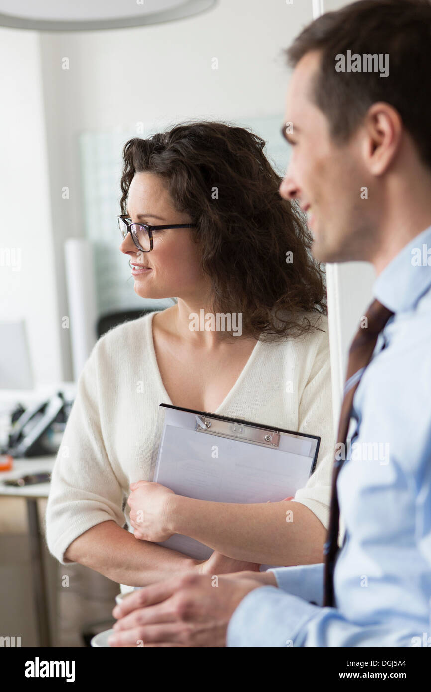 Woman holding clipboard, l'homme en premier plan Photo Stock