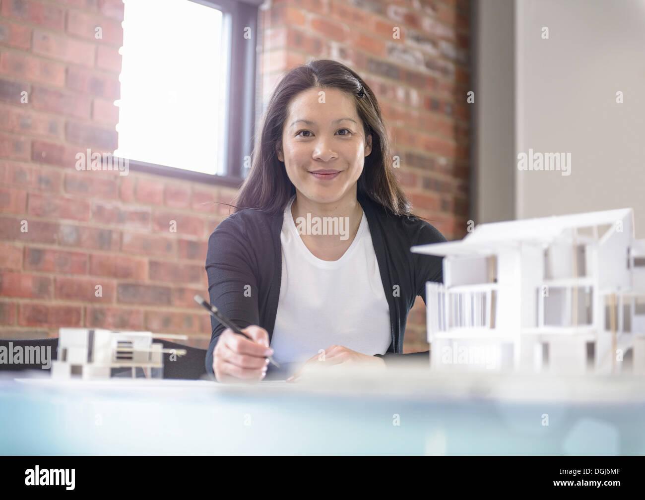 Architect working at desk in office avec le modèle des bâtiments Photo Stock