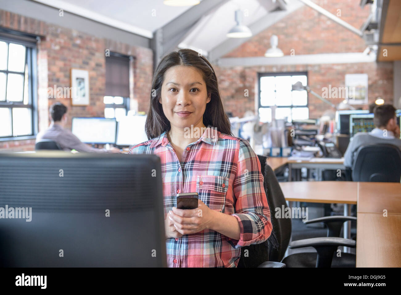 Office worker holding mobile phone at desk in office Photo Stock