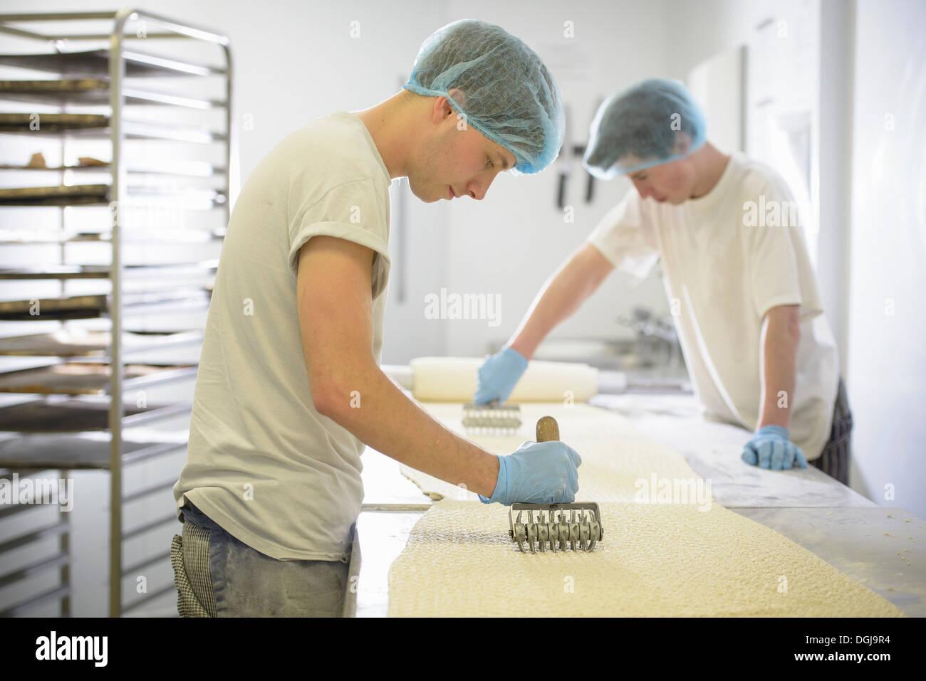 Boulangers dans des vêtements de la préparation durée de pâte Photo Stock