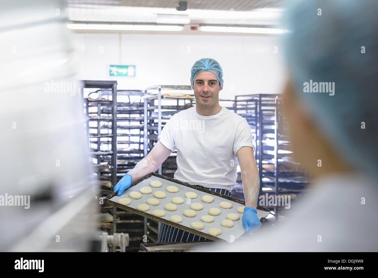Baker holding tray de pâte préparé prêt pour le four Photo Stock