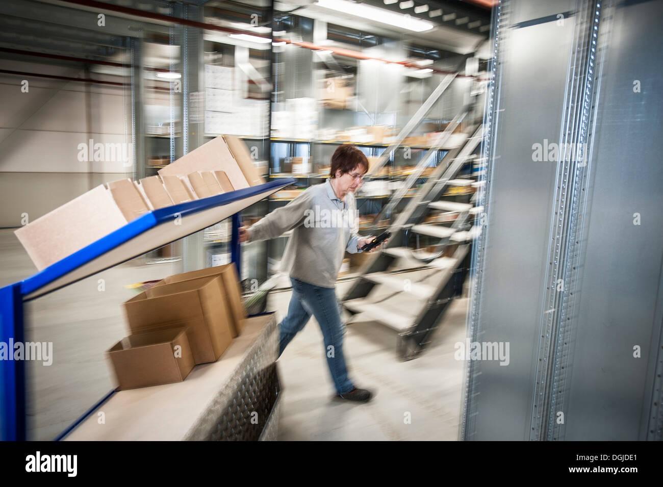 Employé de l'entrepôt femelle panier de chariots mobiles Photo Stock