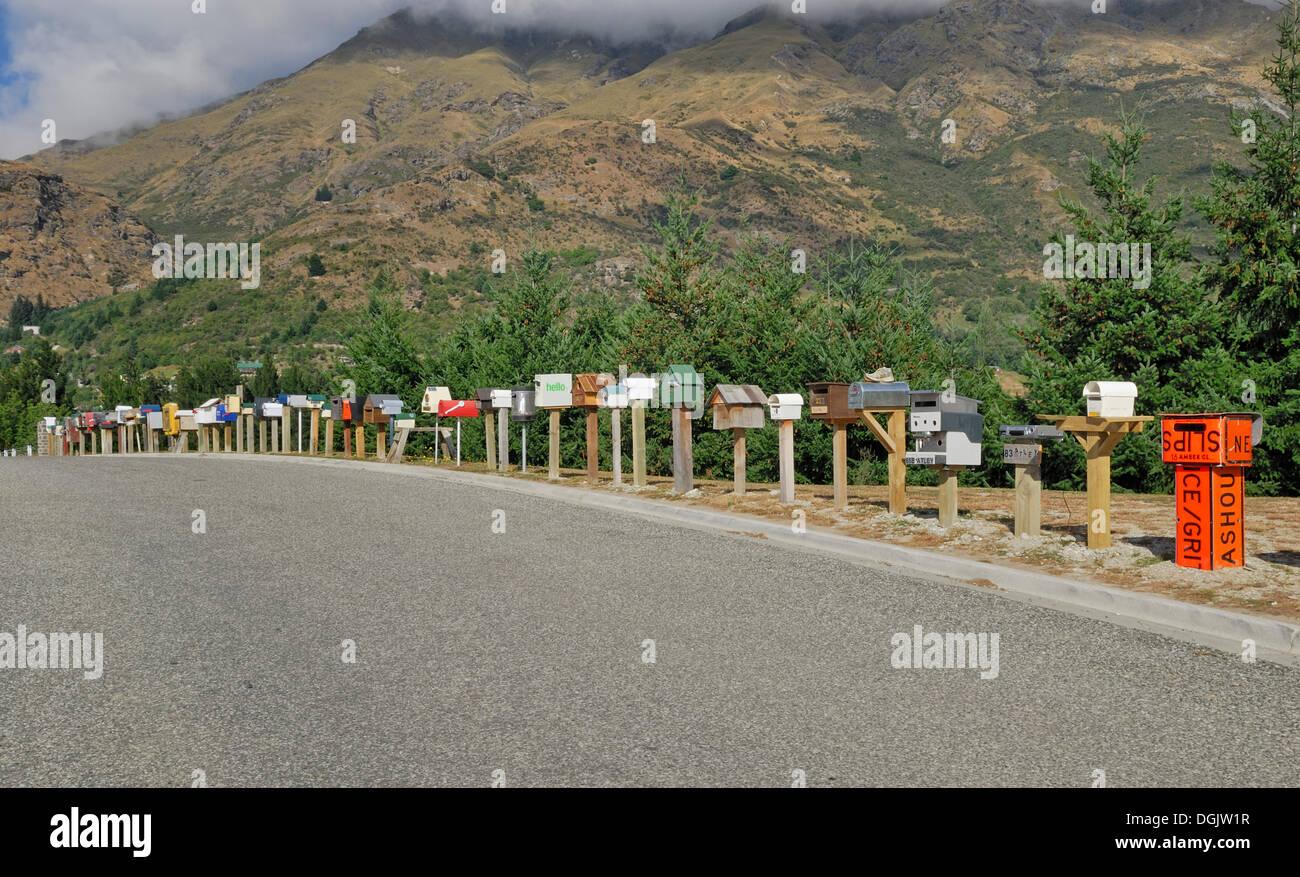 Les boîtes aux lettres individuelles bordant la route d'accès à une nouvelle colonie, Arthurs Point, île du Sud, Nouvelle-Zélande Photo Stock