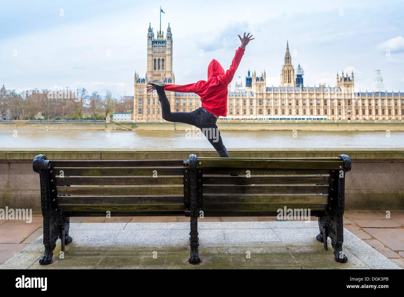 Young male dancer mid air en face du parlement, London, UK Photo Stock