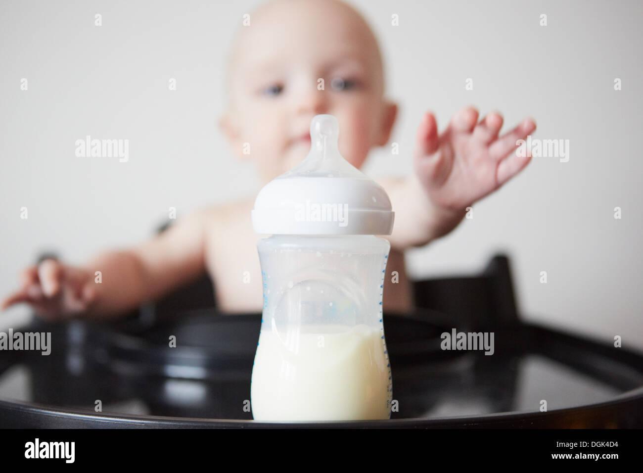 Bébé garçon assis dans une chaise haute pour atteindre le biberon Photo Stock
