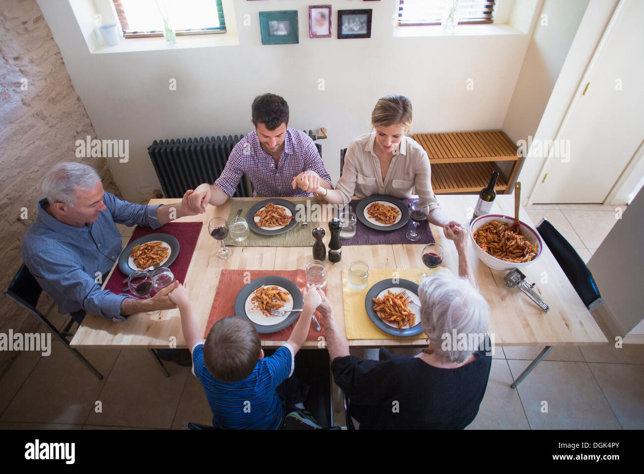 Three generation family holding hands at dinner table Photo Stock
