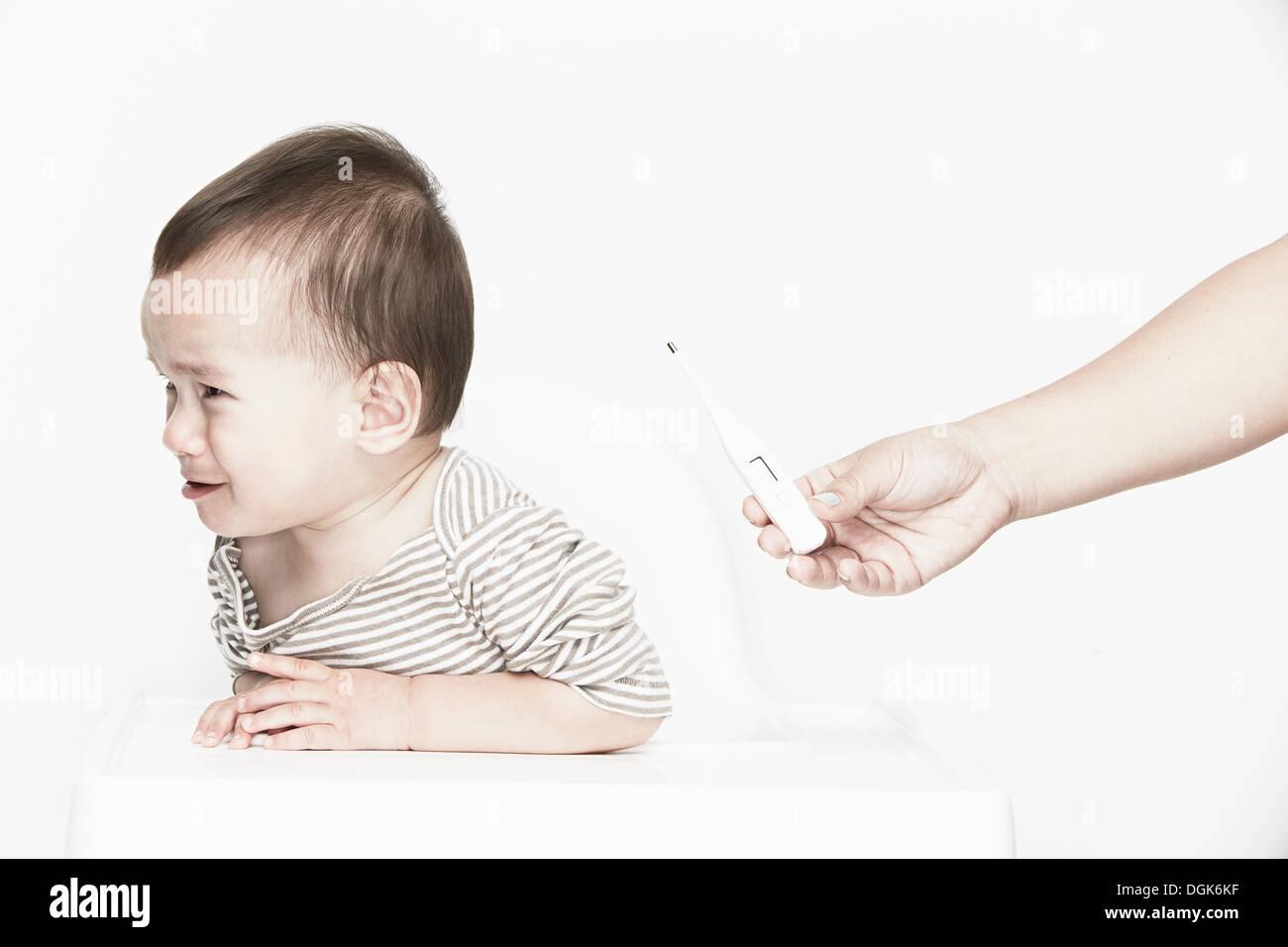 Bébé garçon pleurer, main tenant le thermomètre numérique Photo Stock