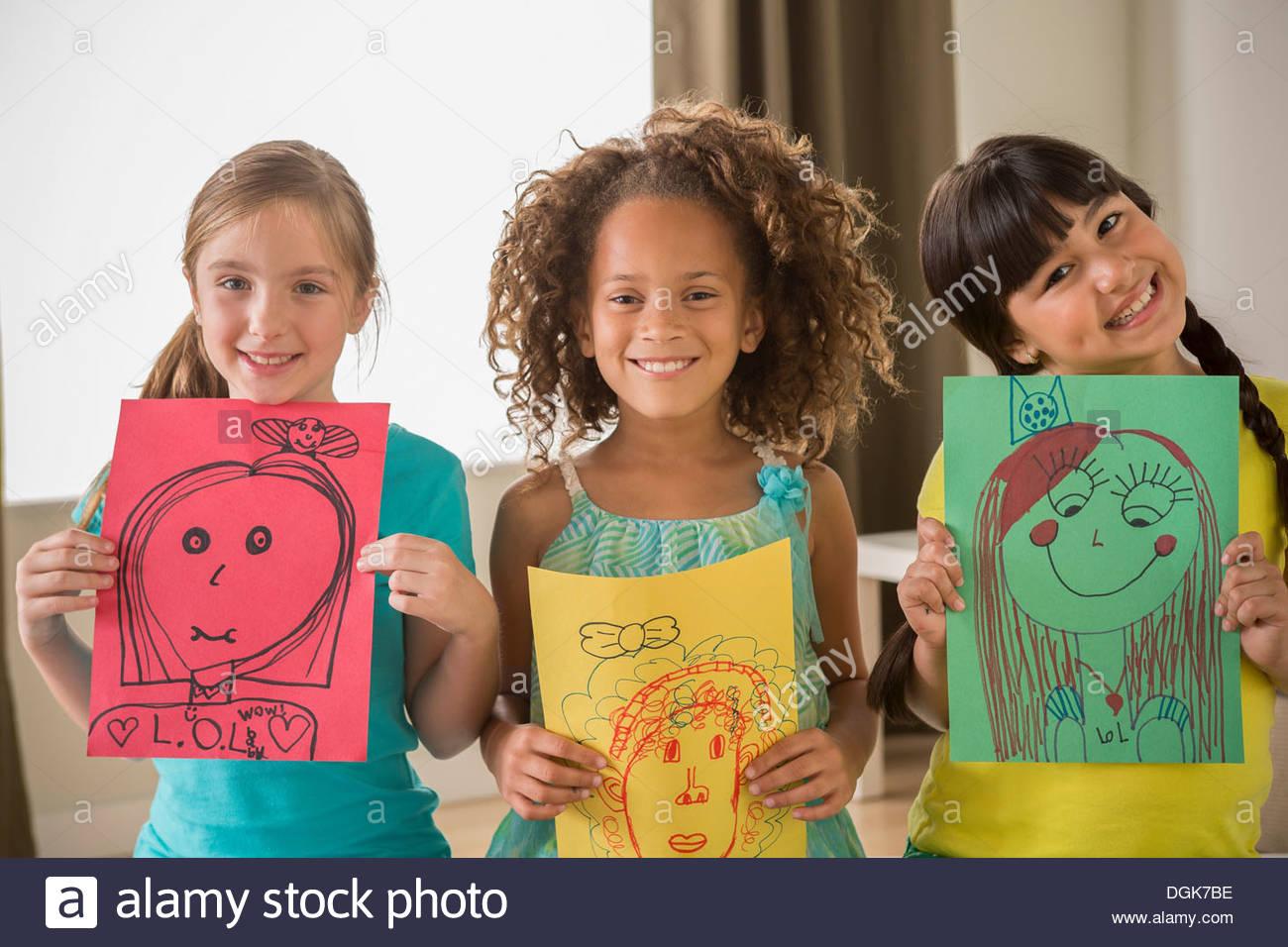 Trois jeunes filles tenant des dessins de visages Photo Stock