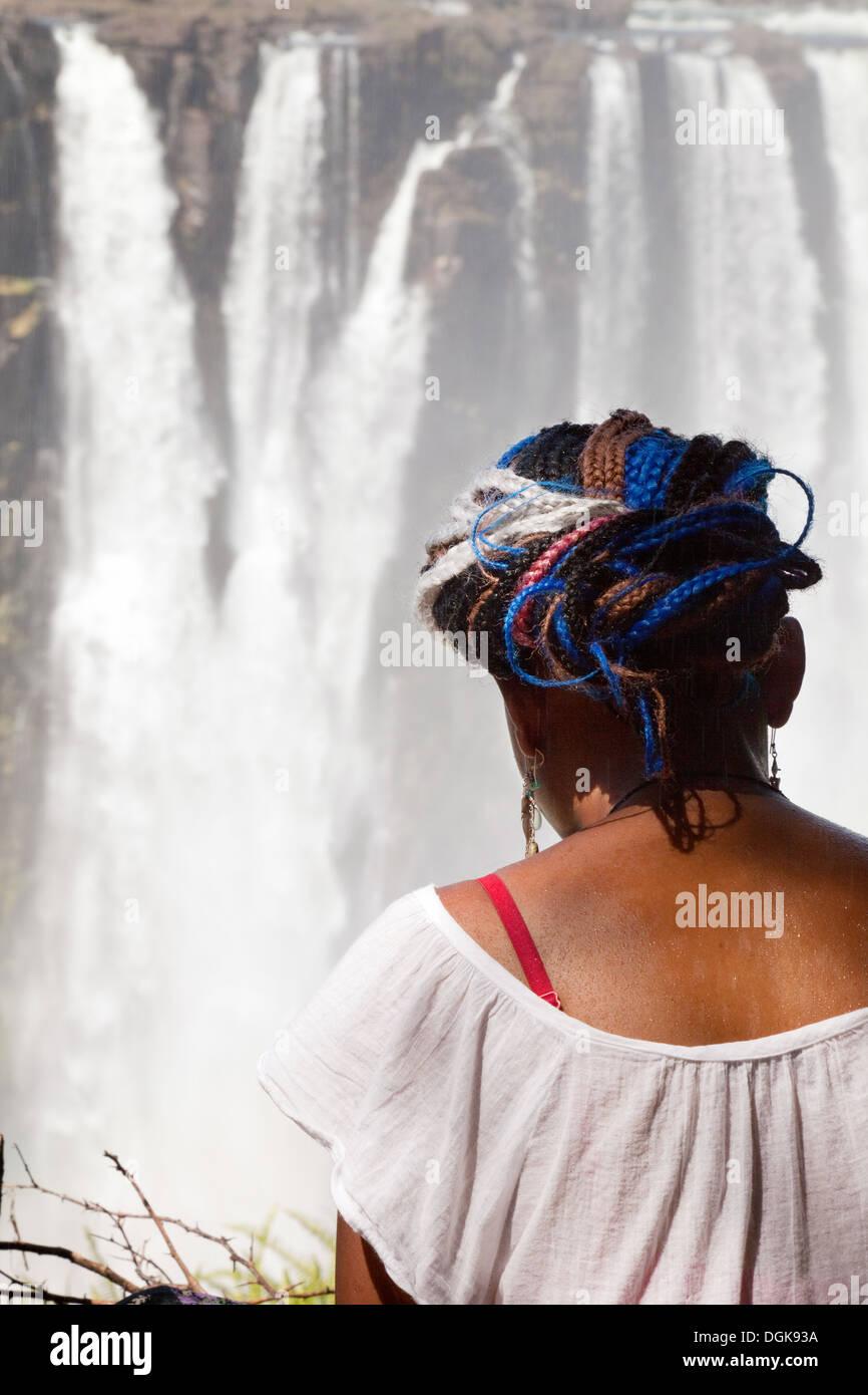 Une fille assise au Zimbabwe à la recherche au Victoria Falls, Zimbabwe, Afrique du Sud Photo Stock