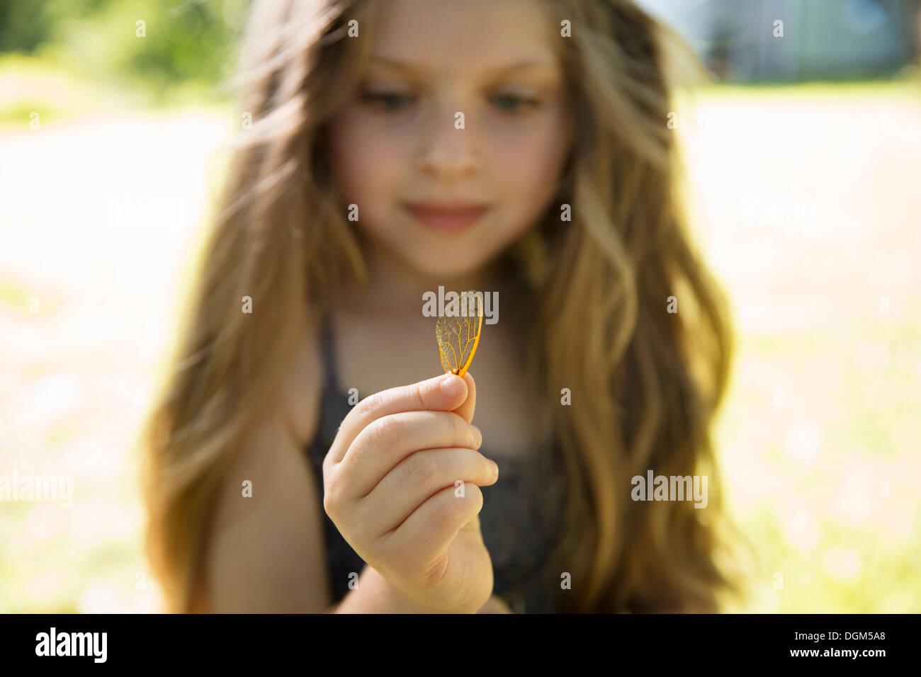Une jeune fille avec de longs blond, tenant une jetée à motifs lacey délicate butterfly wing. Photo Stock
