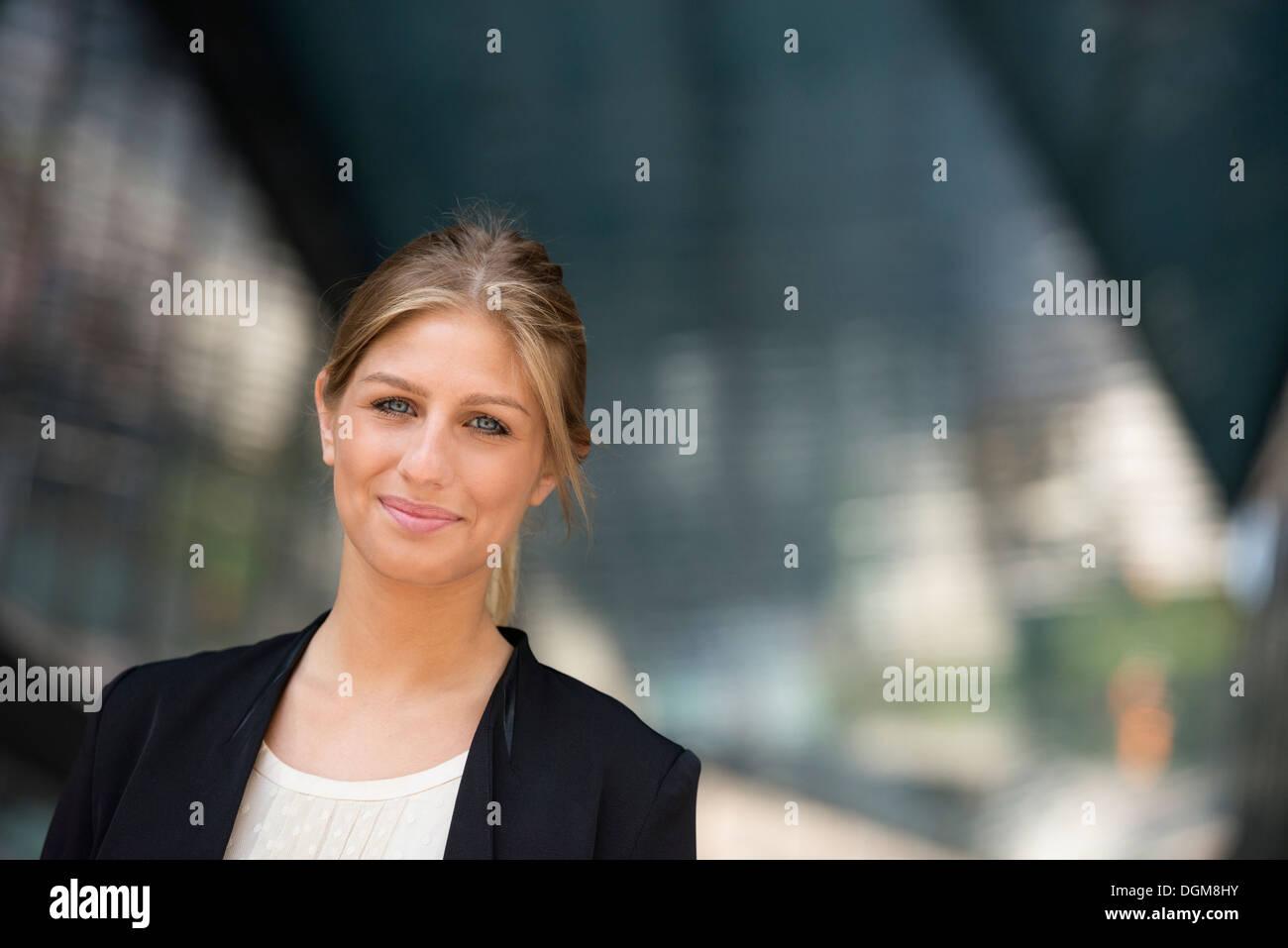 Une jeune femme blonde sur une rue de la ville de New York. Portant une veste noire. Photo Stock