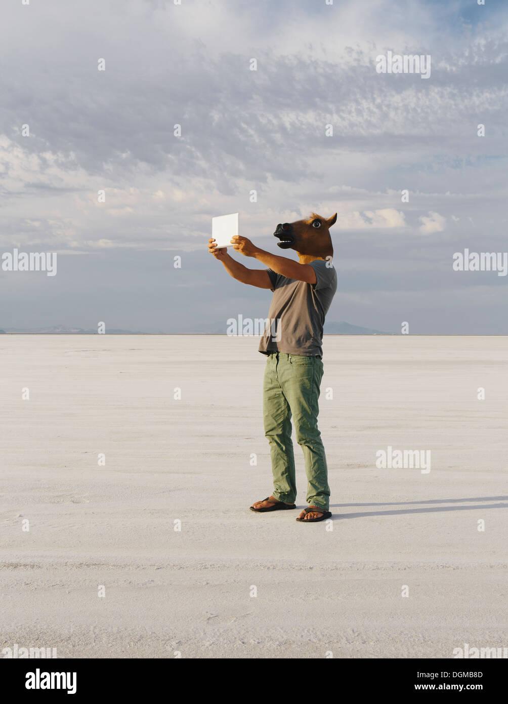 Un homme portant un masque de cheval, de prendre une photo avec une tablette, sur Bonneville Salt Flats. Photo Stock