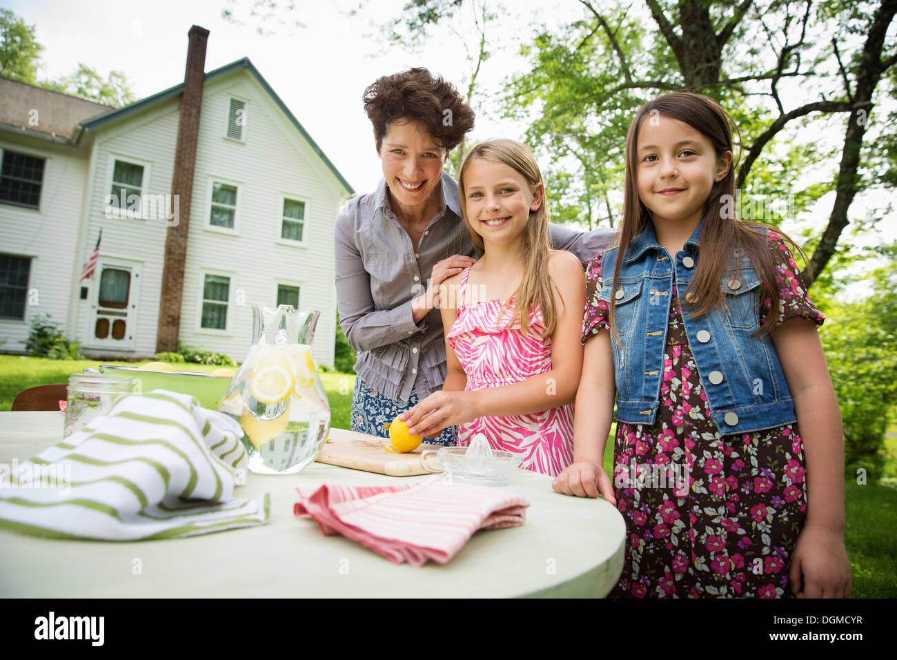 Une réunion de famille d'été dans une ferme. Une femme et deux enfants à l'extérieur par une table, fixant la table. Faire de la limonade. Photo Stock