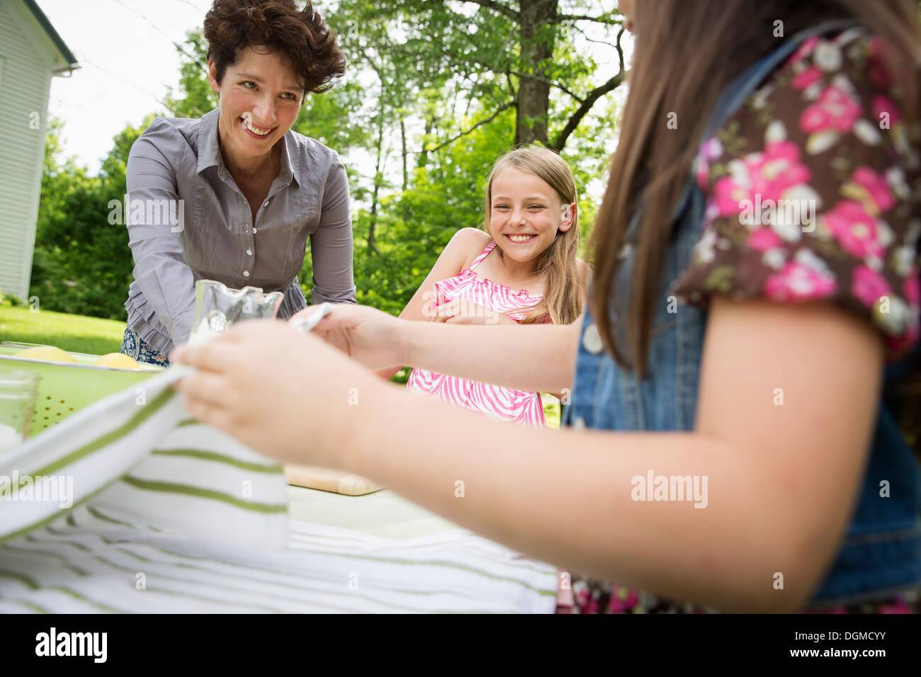 Une réunion de famille d'été dans une ferme. Une femme et deux enfants à l'extérieur par une table, fixant la table. Photo Stock