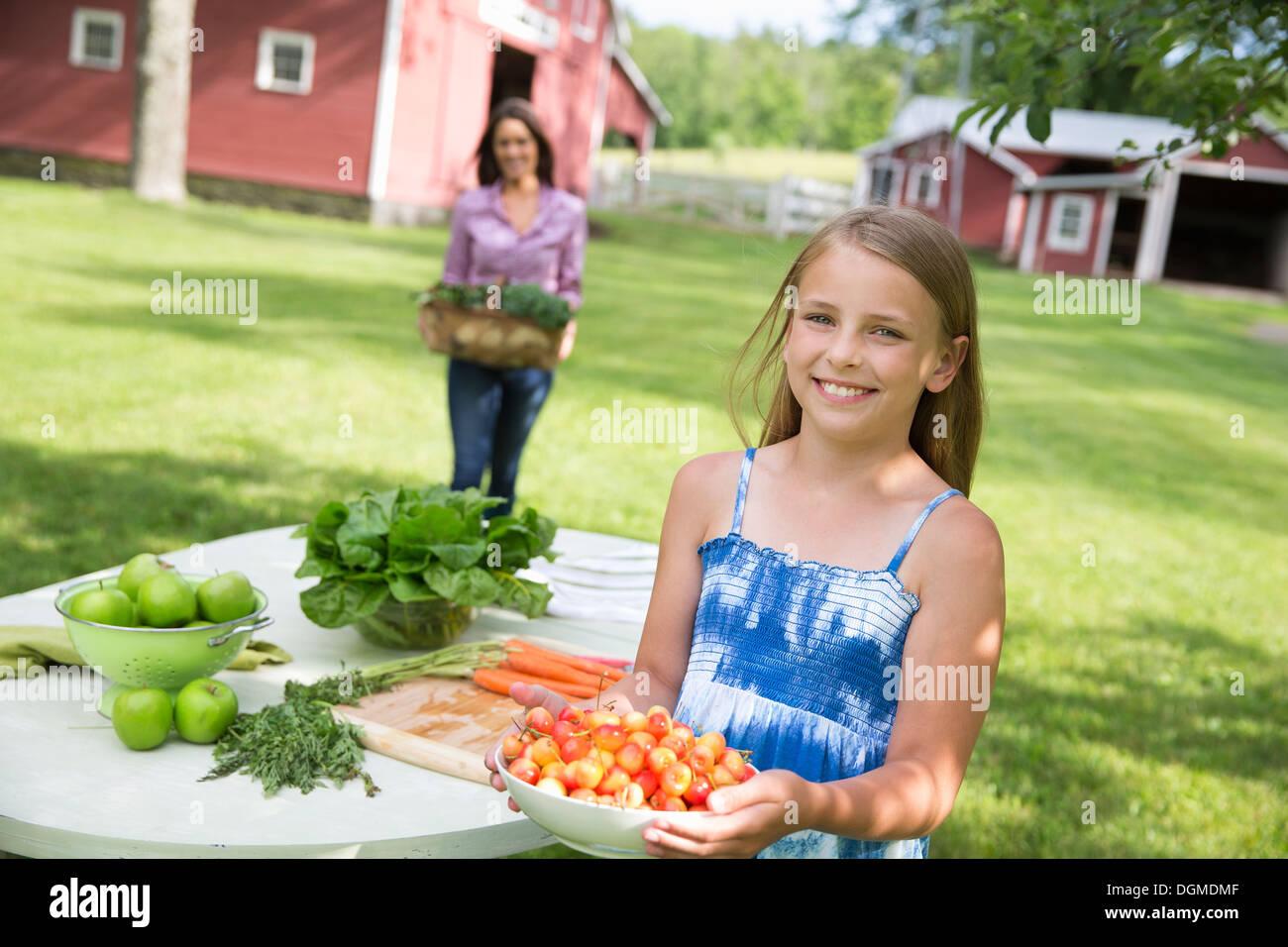 Partie de la famille. Un enfant portant un bol de cerises cueillies fraîches à une table du buffet. Photo Stock