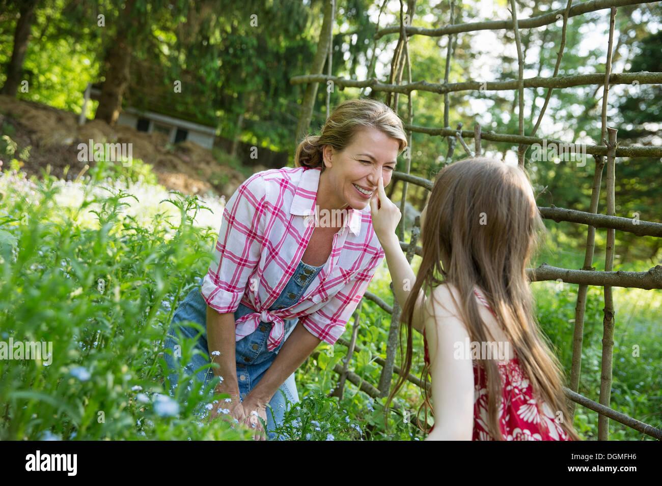 Une mère et sa fille ensemble dans un boîtier de plantes dans un jardin. Les plantes à feuilles vertes. Un enfant de toucher le nez de la femme adultes. Photo Stock