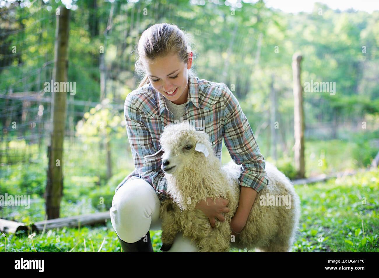 Un adolescent s'agenouiller et de mettre ses bras autour d'une très curly haired chèvre angora. Photo Stock
