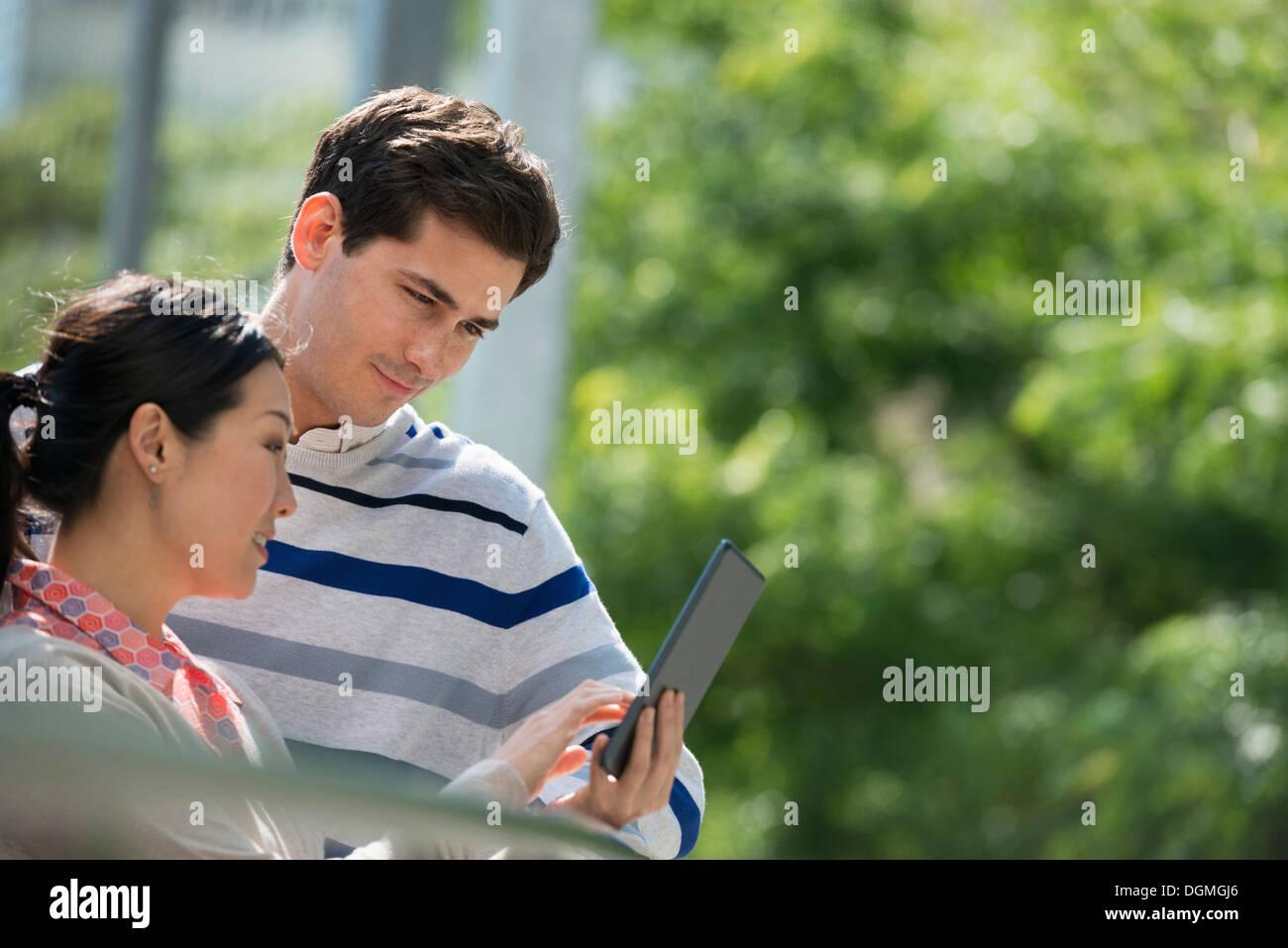 L'été. Les gens d'affaires. Un homme et une femme à l'aide d'une tablette numérique, garder le contact. Banque D'Images