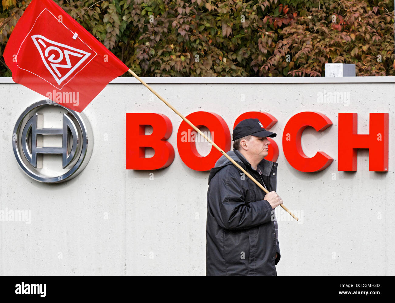 Un travailleur exerçant son drapeau d'IG Metall, en face de l'usine Bosch à Buhl, Baden, Bade-Wurtemberg Photo Stock