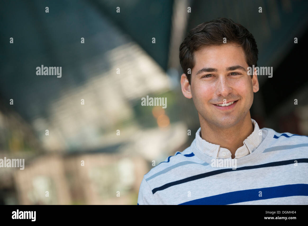 Les gens d'affaires en déplacement. Un jeune homme dans un pullover rayé regardant la caméra. Photo Stock