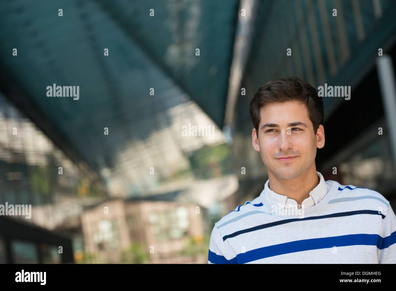 Les gens d'affaires en déplacement. Un jeune homme dans un pullover rayé à la recherche dans la distance. Photo Stock