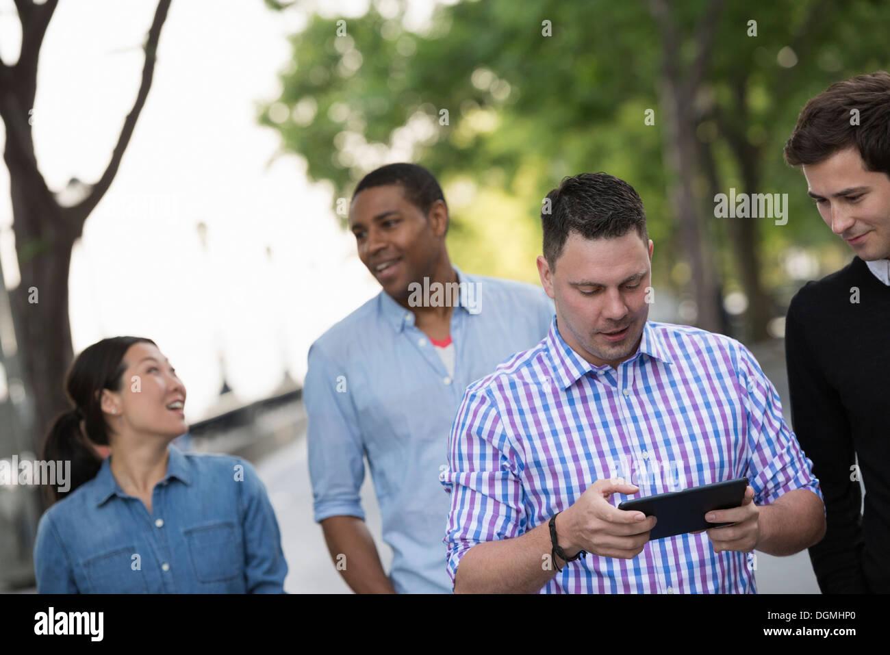L'été dans la ville. Quatre personnes dans un groupe. L'un en utilisant sa tablette numérique. Photo Stock