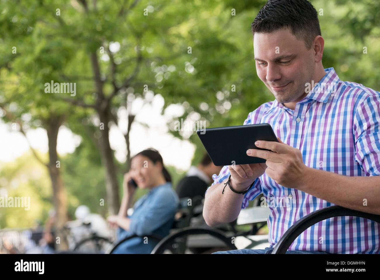 L'été. Une femme et deux hommes assis dans le parc, chacun sur leur propre téléphone ou à l'aide d'une tablette. Photo Stock