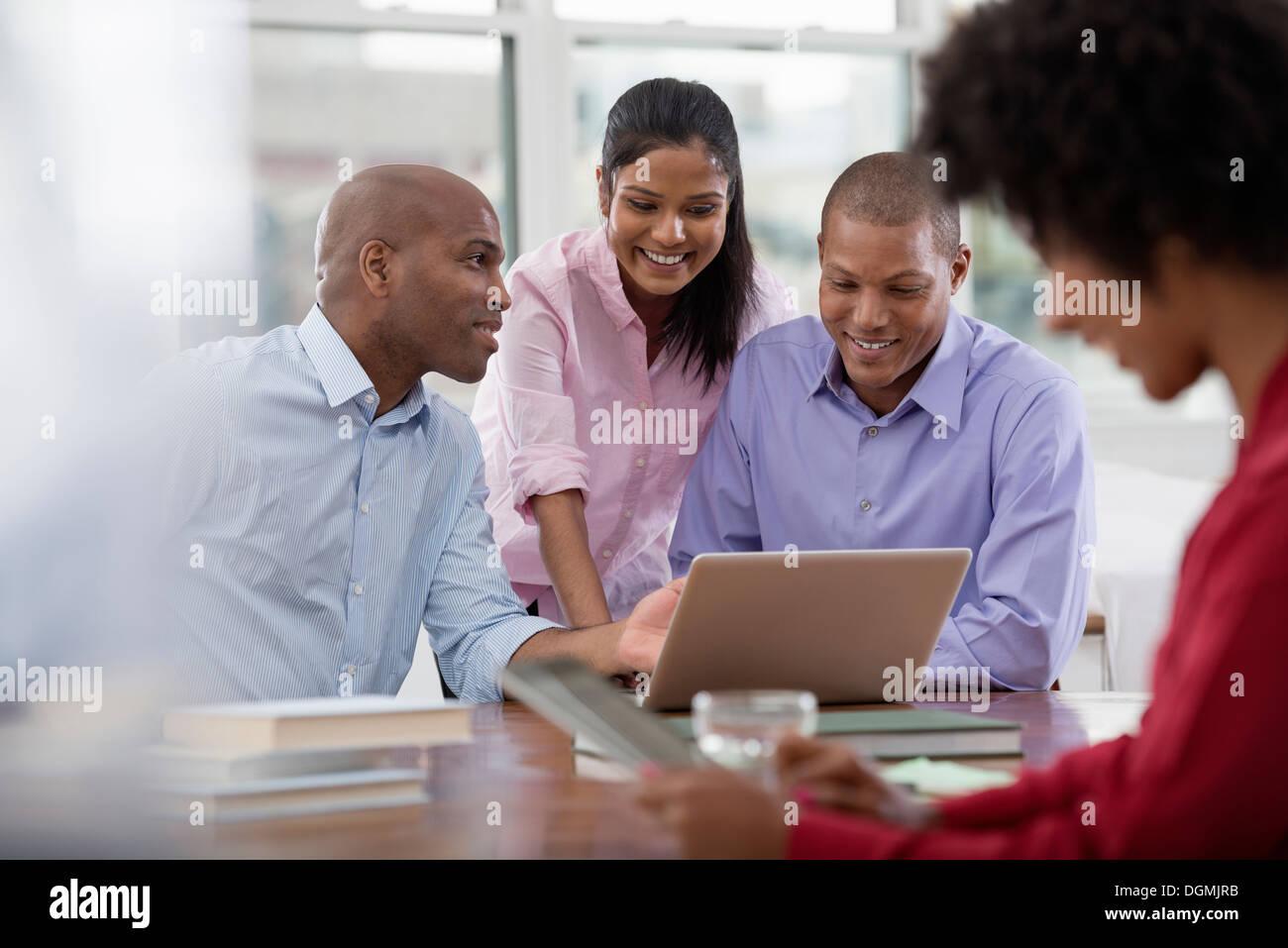 La vie de bureau. Quatre personnes travaillant autour d'une table, à l'aide de tablettes numériques et ordinateurs portables. Photo Stock