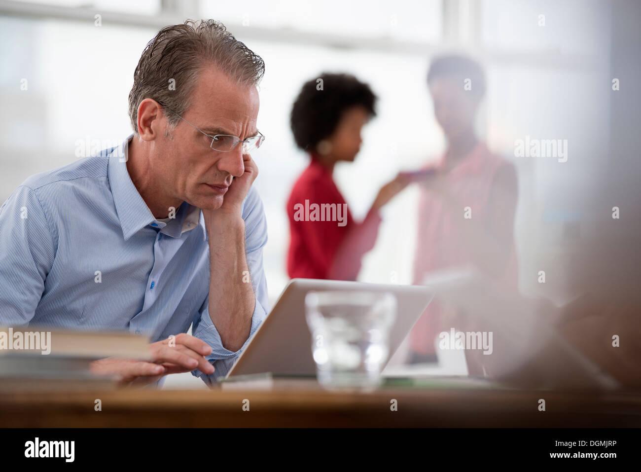 La vie de bureau. Un homme assis à un ordinateur portable s'appuyant sur un bras, et deux femmes à l'arrière-plan. Banque D'Images