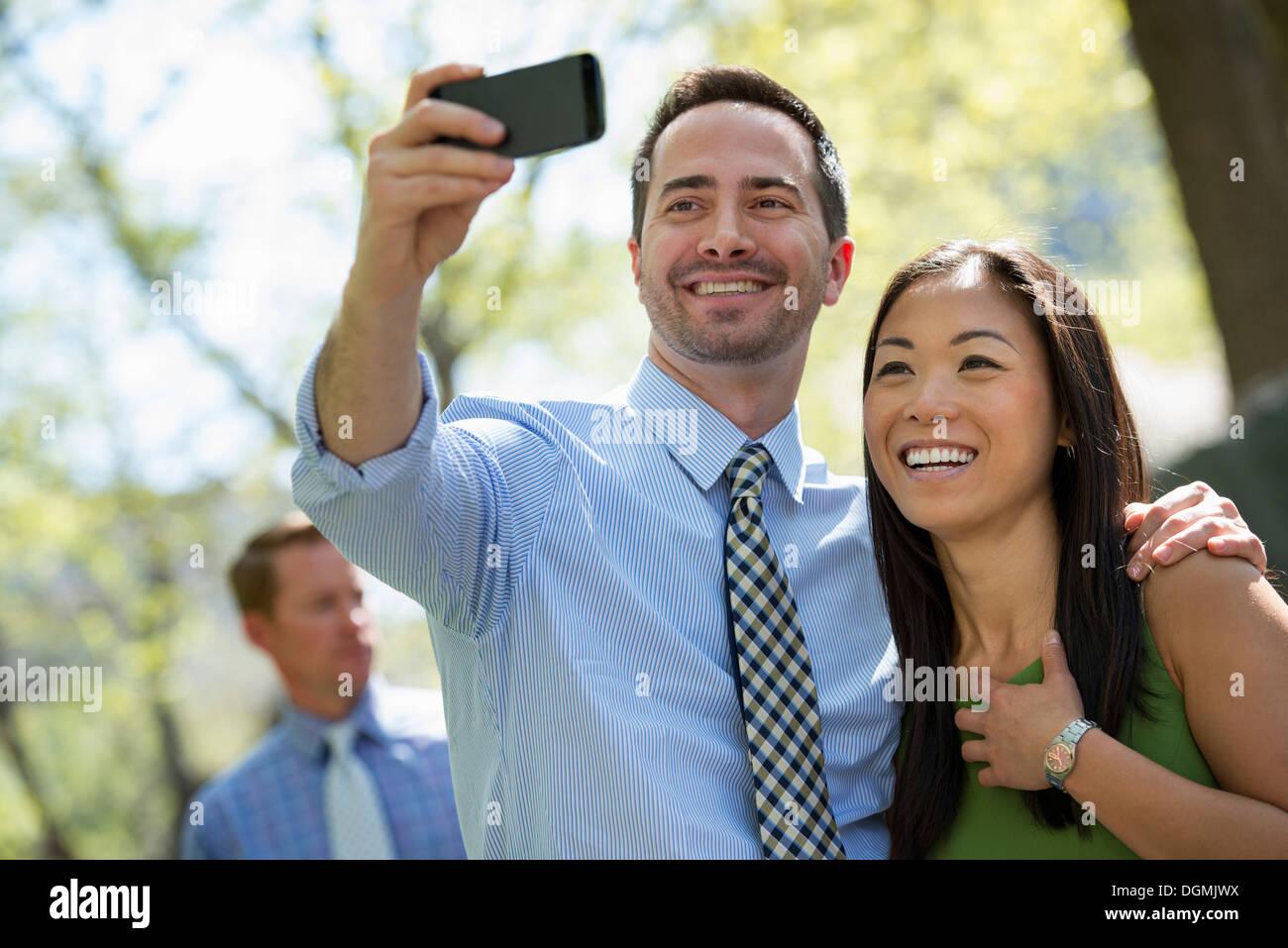 Un couple avec un téléphone intelligent, côte à côte. Un homme dans l'arrière-plan. Photo Stock