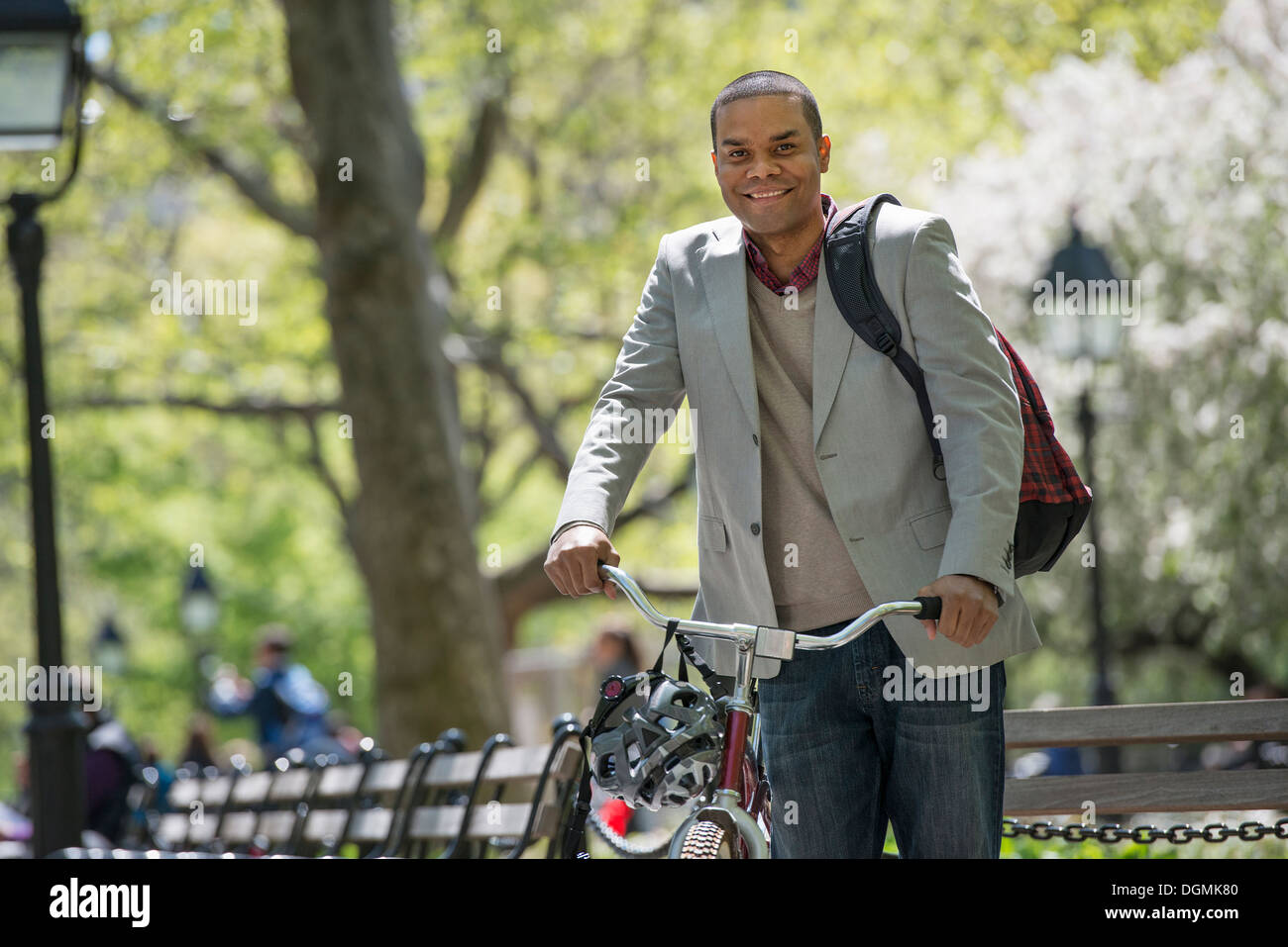 Une famille dans le parc sur une journée ensoleillée. Un homme poussant une bicyclette. Banque D'Images
