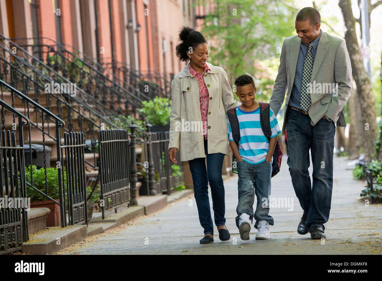 Une famille en plein air dans la ville. Deux parents et un jeune garçon marchant ensemble. Photo Stock
