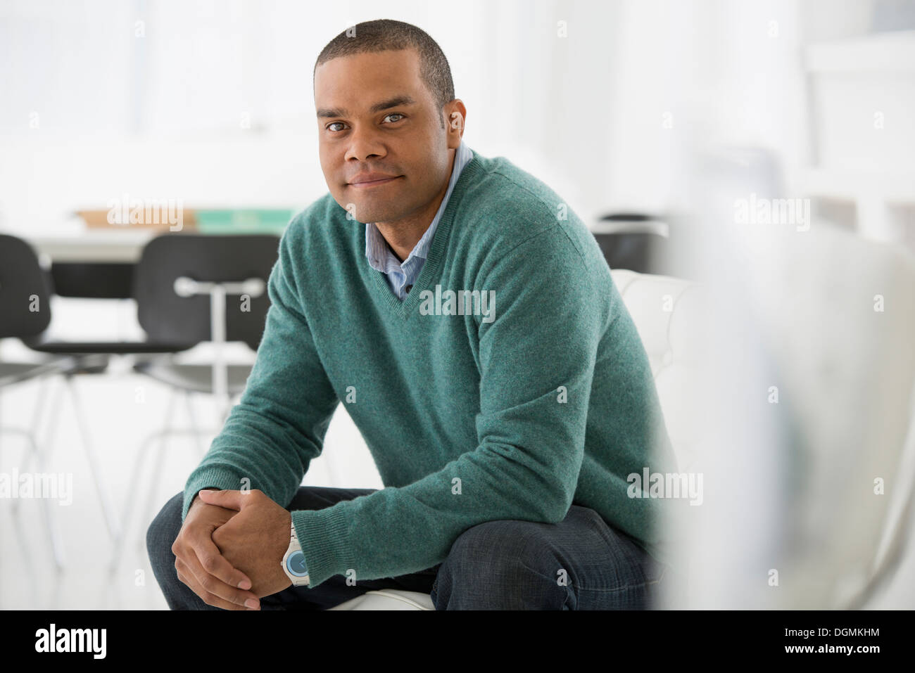 L'entreprise. Un homme assis, les mains jointes dans une ambiance pose assurée. Photo Stock