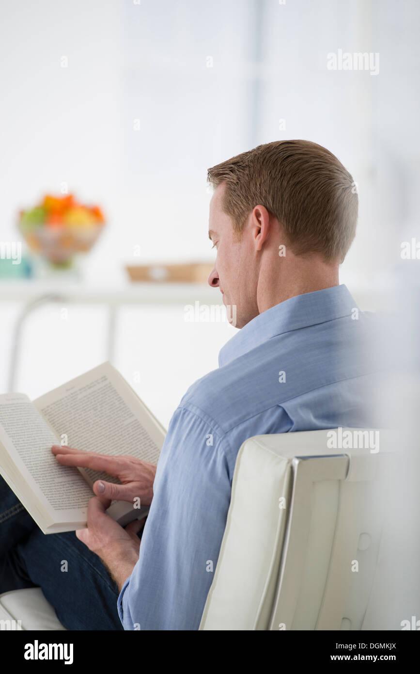 L'entreprise. Un homme assis tenant un livre dans ses mains. La lecture. L'accent sur la page. Vue arrière. Photo Stock