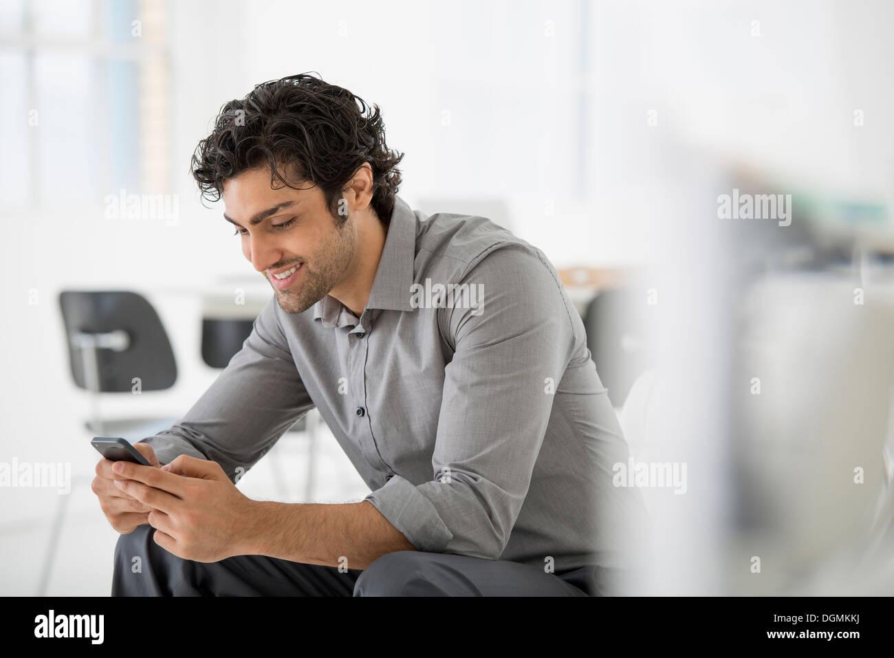 L'entreprise. Un homme assis à la recherche à l'écran sur son téléphone intelligent. Photo Stock