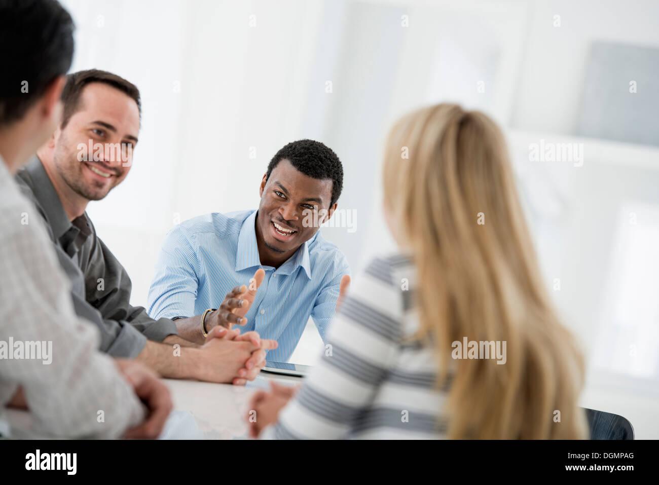 L'intérieur du bureau. Un groupe de quatre personnes, une femme et trois hommes. Photo Stock