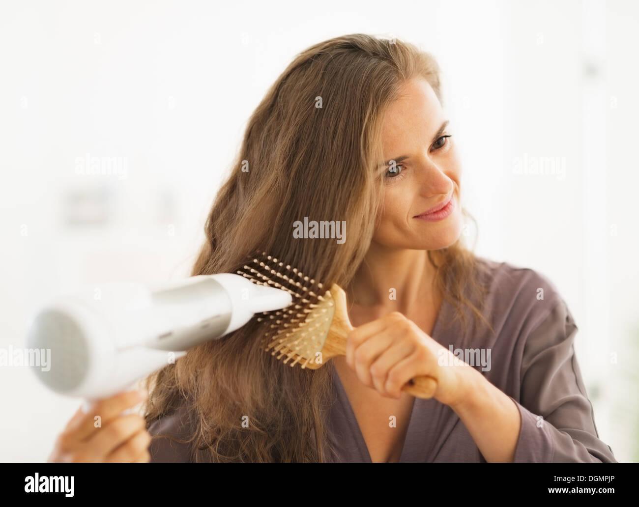 Happy woman le brossage et le séchage des cheveux dans salle de bains coup Photo Stock