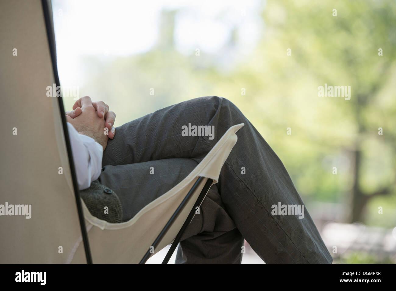 La vie en ville. Un homme assis dans un fauteuil de camping en toile dans le parc. Photo Stock