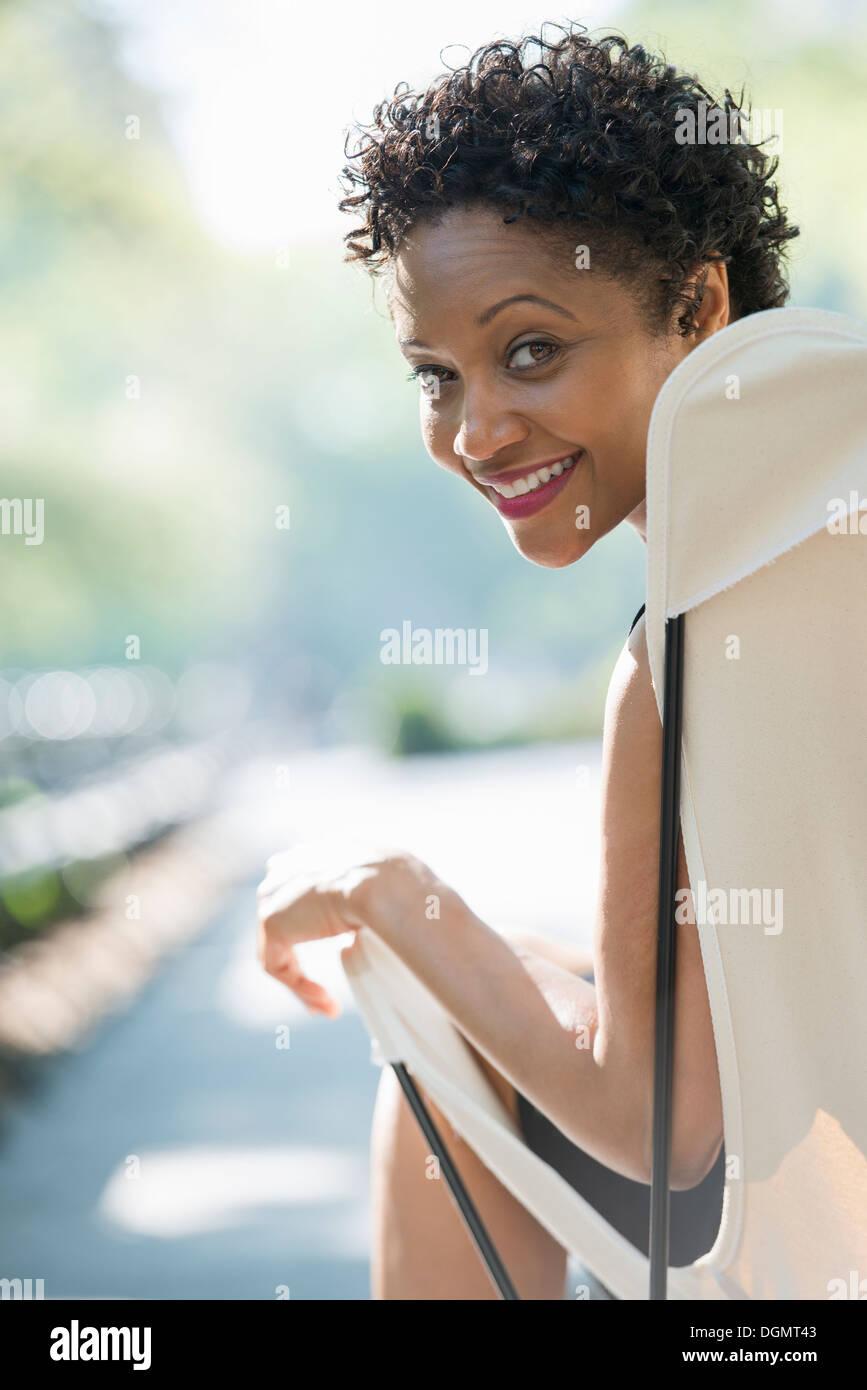 La vie en ville. Une femme assise dans un fauteuil de camping dans un parc à par-dessus son épaule. Photo Stock