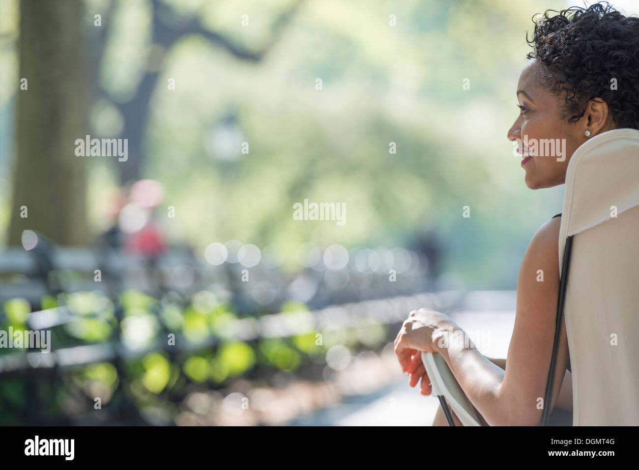 La vie en ville. Une femme assise dans un fauteuil de camping dans un parc de la ville. Photo Stock